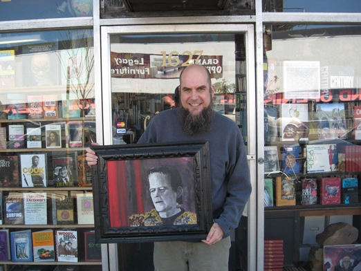 Footnote Books owner Troy Beaver outside his store holding Shel's painting of Frankenstein's Monster.